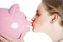 Blonde junge Frau, die ein Sparschwein küsst Stockfotografie