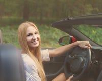 Blonde junge Frau, die ein Sportauto fährt Lizenzfreie Stockbilder