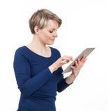 Blonde junge Frau, die eine Berührungsfläche verwendet Lizenzfreies Stockfoto