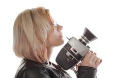 Blonde, junge Frau, die eine Filmkamera anhält Stockfoto
