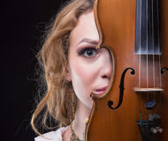 Blonde junge Frau, die hinter Violine sich versteckt Stockfoto