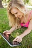 Blonde junge Frau, die ihre Tablette verwendet Stockbilder