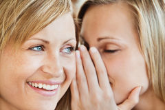 Blonde junge Frau, die ihrem Freund ein Geheimnis erklärt Lizenzfreie Stockbilder