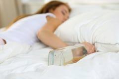 Blonde junge Frau, die im Bett tot betrunken liegt Lizenzfreie Stockfotografie