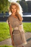 Blonde junge Frau, die im Park steht Lizenzfreies Stockfoto