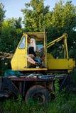 Blonde junge Frau, die im Traktor sitzt Stockfoto