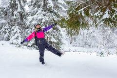Blonde junge Frau, die im Winterwald steht Lizenzfreies Stockbild