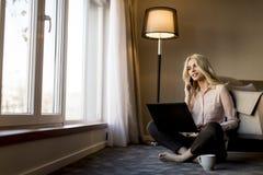 Blonde junge Frau, die Laptop und Handy beim Sitzen von O verwendet Lizenzfreie Stockfotos