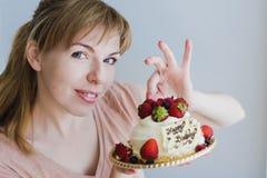 Blonde junge Frau, die mit Geburtstagskuchen aufwirft Lizenzfreie Stockfotos