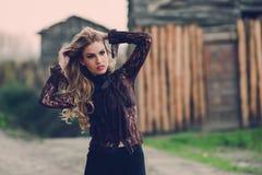 Blonde junge Frau, die mit ihrem gelockten Haar spielt Stockfotos