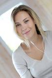 Blonde junge Frau, die Musik hört Lizenzfreie Stockfotografie