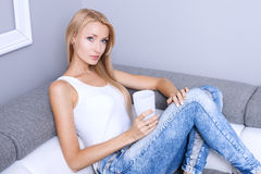 Blonde junge Frau, die sich zu Hause entspannt Stockfotos