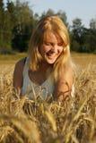 Blonde junge Frau, die vom Inneren lacht Lizenzfreie Stockbilder
