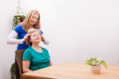 Blonde junge Frau, die weibliche Seniorkopfhaut massiert Lizenzfreies Stockfoto