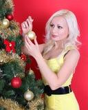 Blonde junge Frau, die Weihnachtsbaum über Rot verziert Lizenzfreies Stockfoto