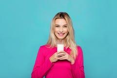 Blonde junge Frau ein Glas Milch auf Blau Stockbild