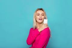 Blonde junge Frau ein Glas Milch auf Blau Stockfoto
