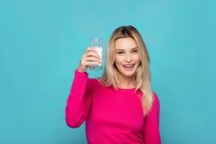 Blonde junge Frau ein Glas Milch auf Blau Lizenzfreies Stockbild