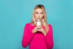 Blonde junge Frau ein Glas Milch auf Blau Stockbilder