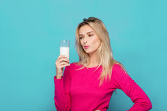 Blonde junge Frau ein Glas Milch auf Blau Stockfotos