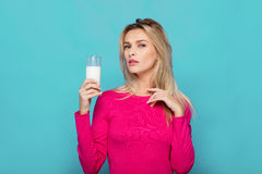 Blonde junge Frau ein Glas Milch auf Blau Lizenzfreies Stockfoto