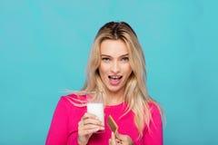 Blonde junge Frau ein Glas Milch auf Blau Stockfotografie