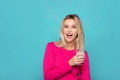 Blonde junge Frau ein Glas Milch auf Blau Lizenzfreie Stockfotos