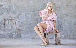 Blonde junge Frau in einem Kleid Stockfotografie