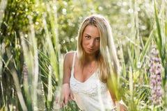 Blonde junge Frau in einer Grasnahaufnahme Lizenzfreie Stockfotografie