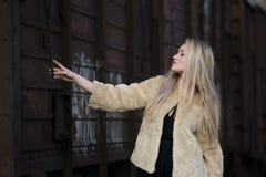 Blonde junge Frau gegen einen Lastwagenzug Stockbild
