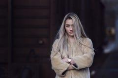 Blonde junge Frau gegen einen Lastwagenzug Stockfotografie