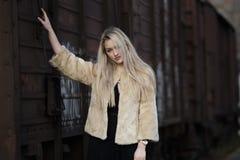 Blonde junge Frau gegen einen Lastwagenzug Lizenzfreies Stockfoto