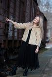 Blonde junge Frau gegen einen Lastwagenzug Stockfoto