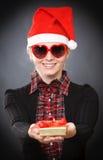 Blonde junge Frau gibt Geschenk Lizenzfreies Stockfoto