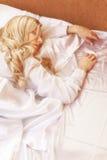 Blonde junge Frau im Bett Stockfoto