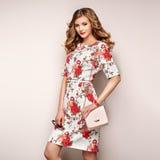 Blonde junge Frau im Blumenfrühlingssommerkleid Stockfotos