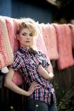 Blonde junge Frau im Cowboyhemd und -Blue Jeans Lizenzfreies Stockfoto