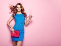 Blonde junge Frau im eleganten blauen Kleid Stockfoto