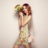 Blonde junge Frau im eleganten Blumenkleid Stockbild