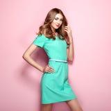 Blonde junge Frau im eleganten grünen Kleid Stockfotografie