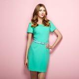 Blonde junge Frau im eleganten grünen Kleid Stockfoto