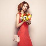 Blonde junge Frau im eleganten roten Kleid Stockbild