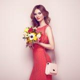 Blonde junge Frau im eleganten roten Kleid Stockfotografie