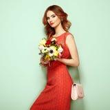 Blonde junge Frau im eleganten roten Kleid Stockfoto