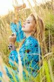 Blonde junge Frau im Kleid sitzt auf Gras und bewegt Hand wellenartig Lizenzfreie Stockbilder