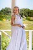 Blonde junge Frau im langen weißen Kleid, das in der Nische steht Stockfoto