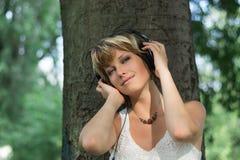 Blonde junge Frau im Park an hörend Musik Lizenzfreies Stockbild