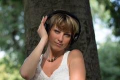Blonde junge Frau im Park an hörend Musik Stockfoto