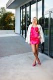 Blonde junge Frau im rosa Kleid und in der weißen Mantelaufstellung Stockfotos