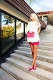 Blonde junge Frau im rosa Kleid und in der weißen Mantelaufstellung Lizenzfreie Stockfotos